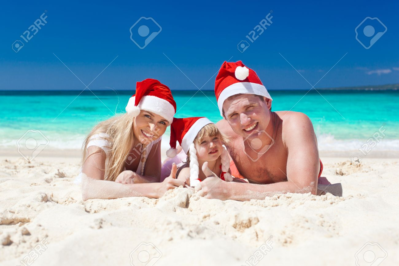 Happy family on beach in Santa hats, mother, father and little daughter Stock Photo - 22311604