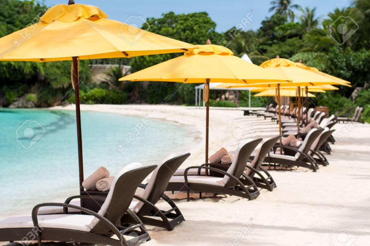 Sun umbrellas and beach chairs on tropical beach, Philippines, Boracay Stock Photo - 22768982