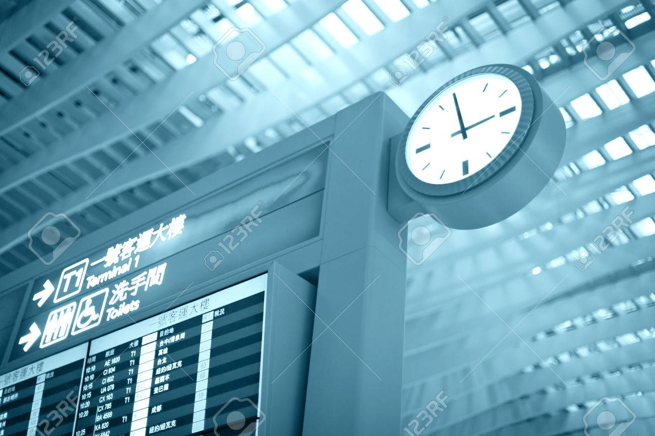Big airport clock close to arrival board in airport terminal. Travel concept. Stock Photo - 23221996