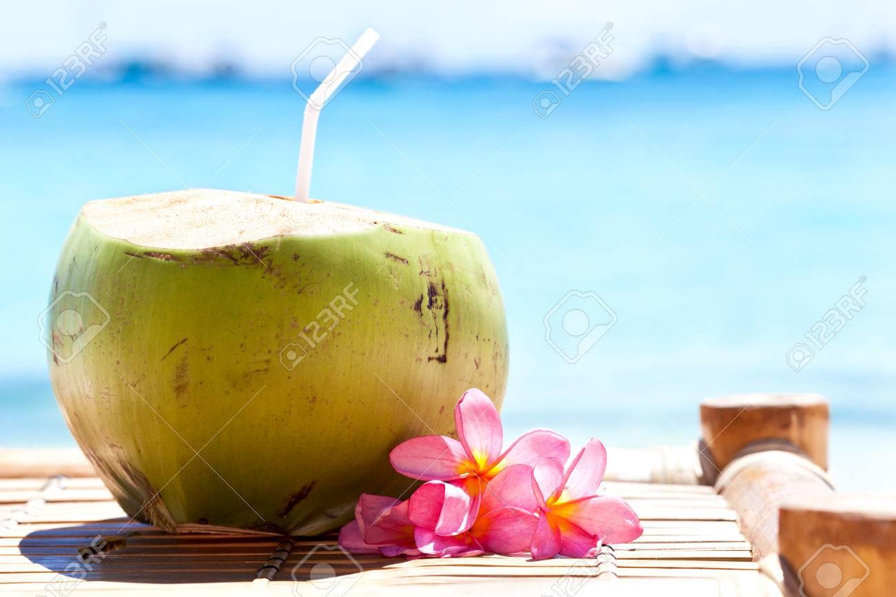 Tropical fresh coconut cocktail decorated plumeria on white beach Stock Photo - 23537497