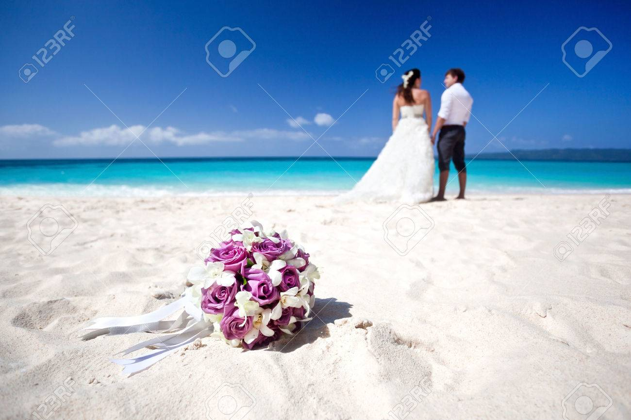 Wedding bouquet on wedding couple kissing at the beach Stock Photo - 25107446