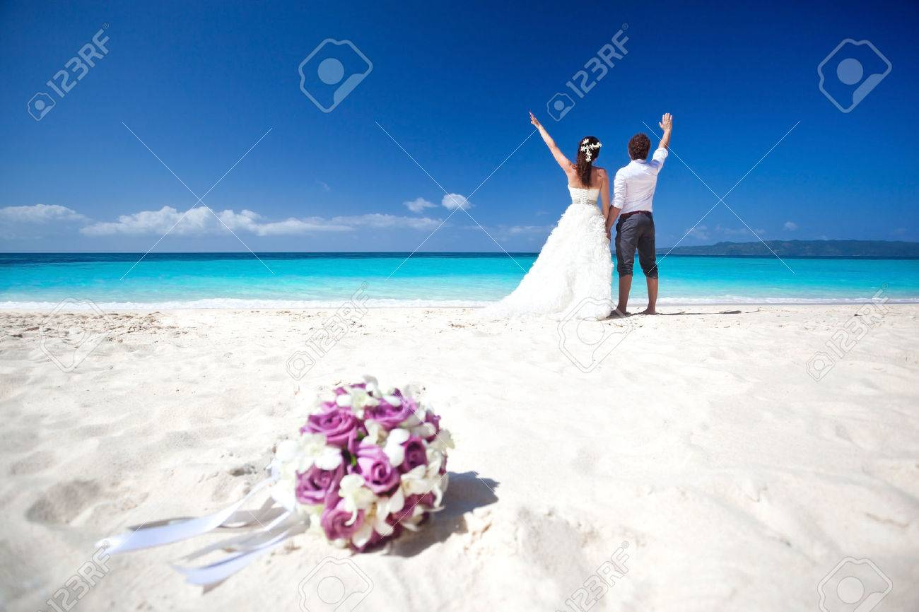 Wedding bouquet on wedding couple background, kissing at the beach Stock Photo - 25086188