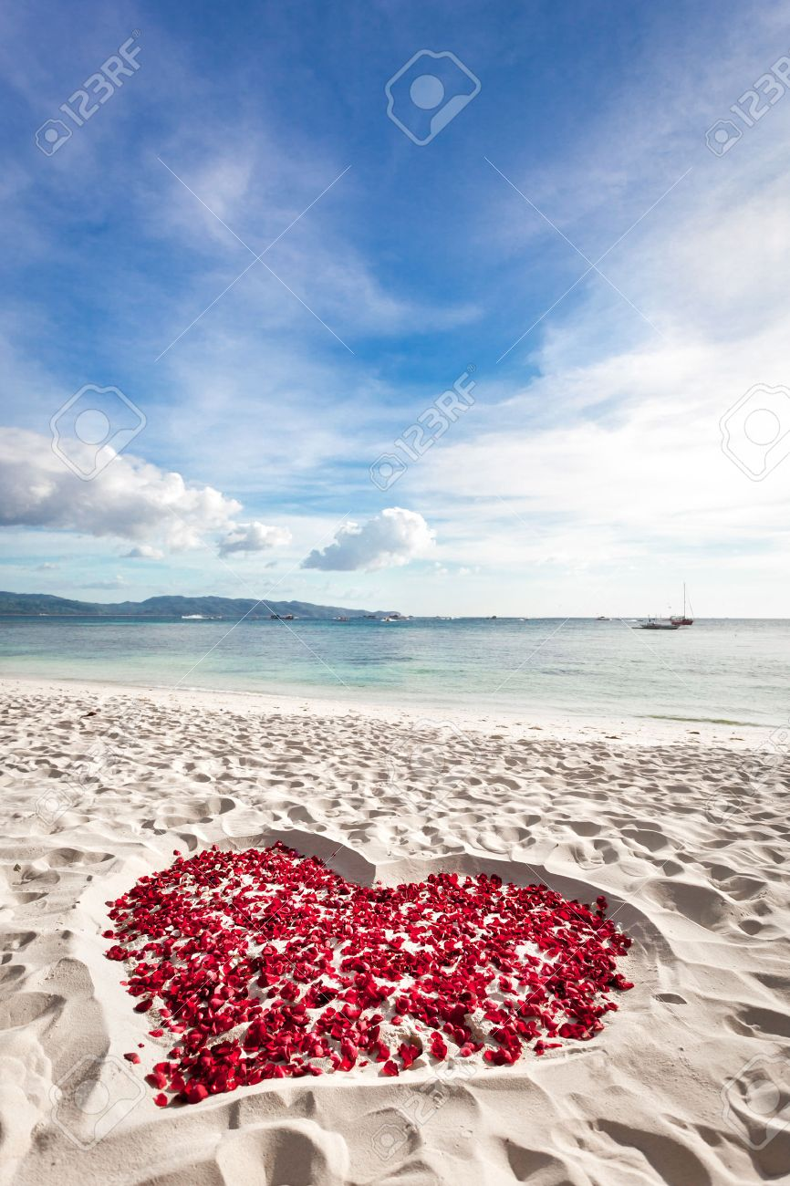 Heart of roses petals on tropical sandy beach. Nobody. Love concept Stock Photo - 25253345