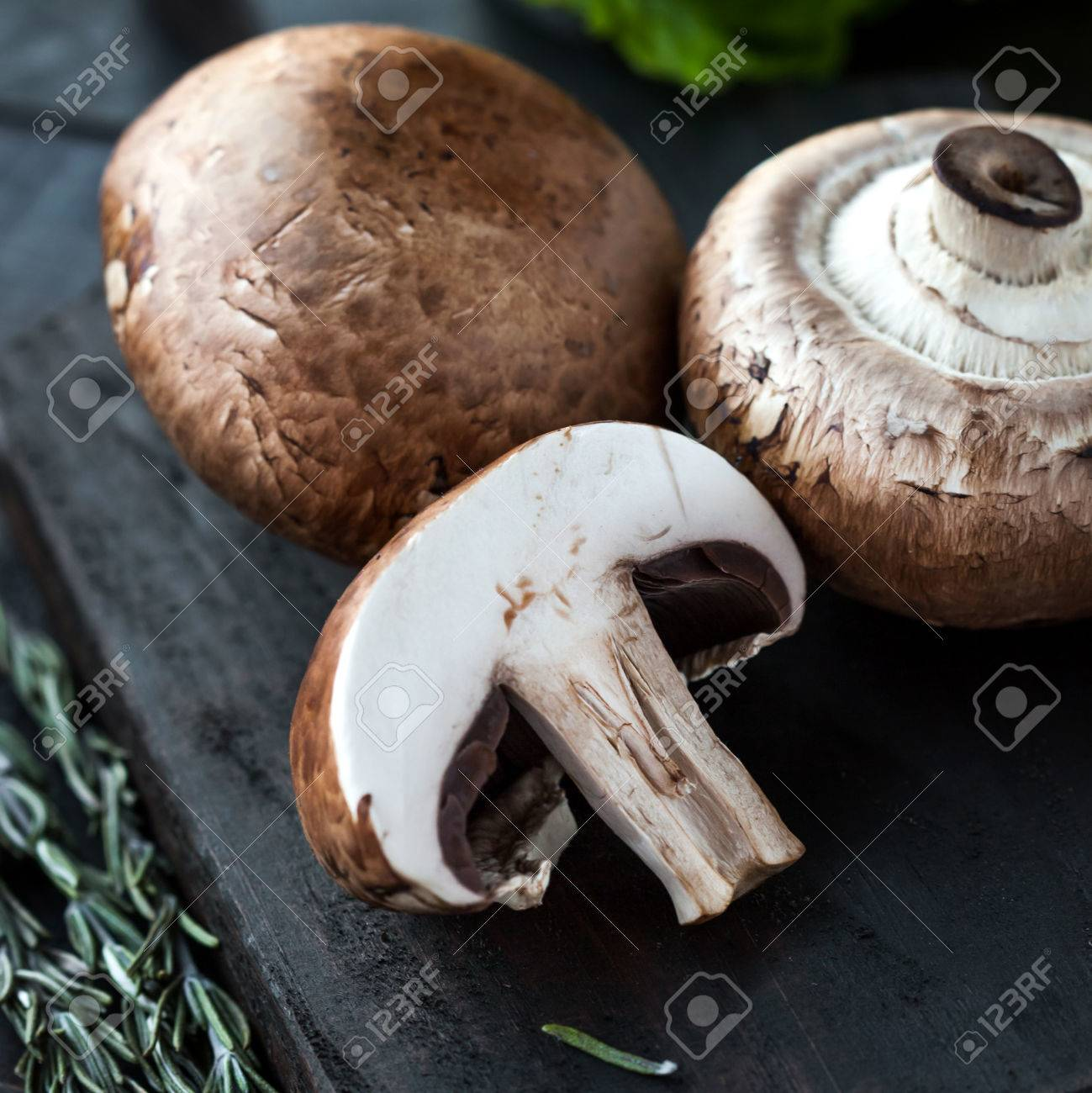 Raw Portobello Mushrooms With Rosemary On Cutting Board On Dark Stock Photo Picture And Royalty Free Image Image 36490625