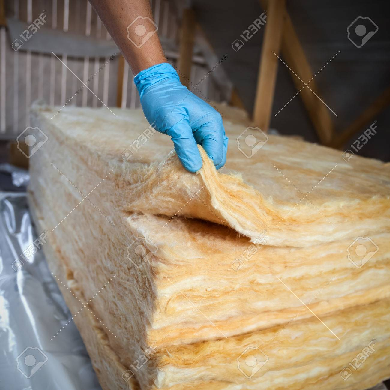 Hand in gloves holding mineral wool,  building under construction Stock Photo - 37569641