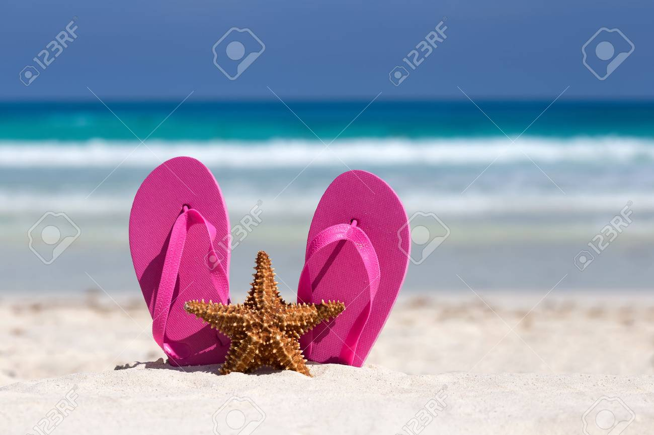 a2ed1a7b04f0 Pink flip flops and starfish on white sandy beach. Summer vacation concept  Stock Photo -