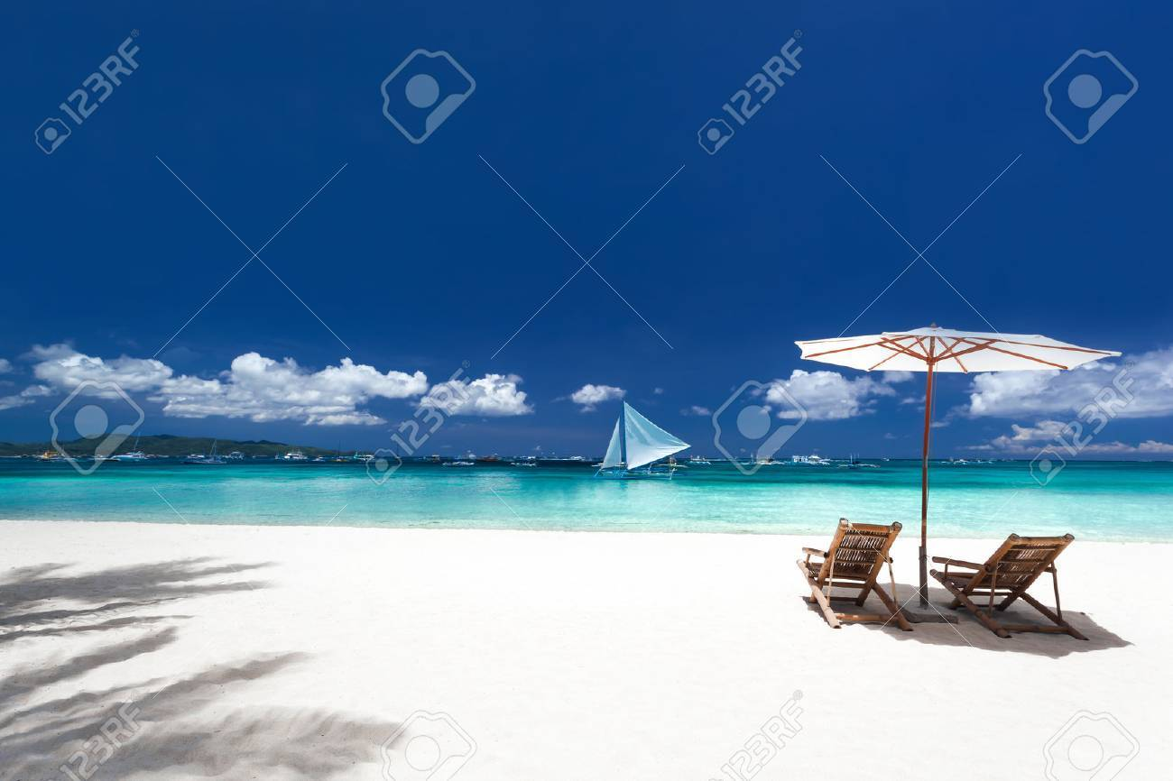 Sun umbrellas and wooden beds on tropical beach. Caribbean vacation Stock Photo - 43175226