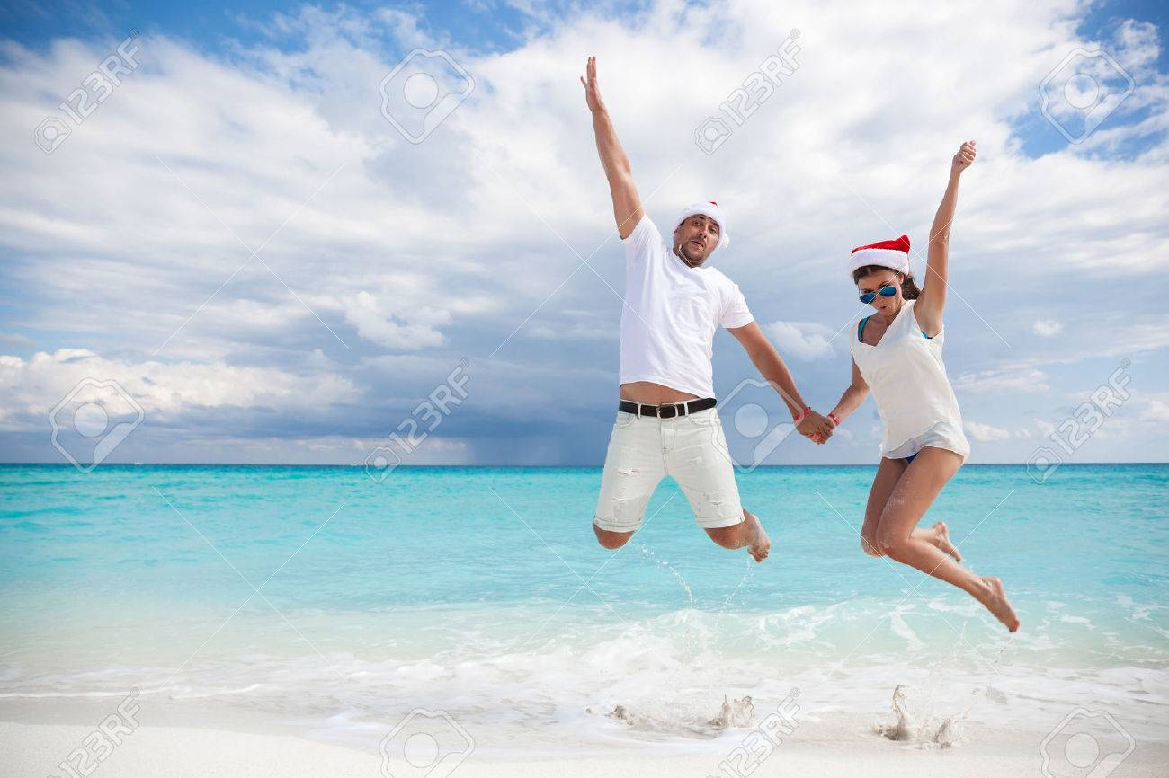 Happy couple celebrating Christmas on beach, jumping in the air Stock Photo - 43177285