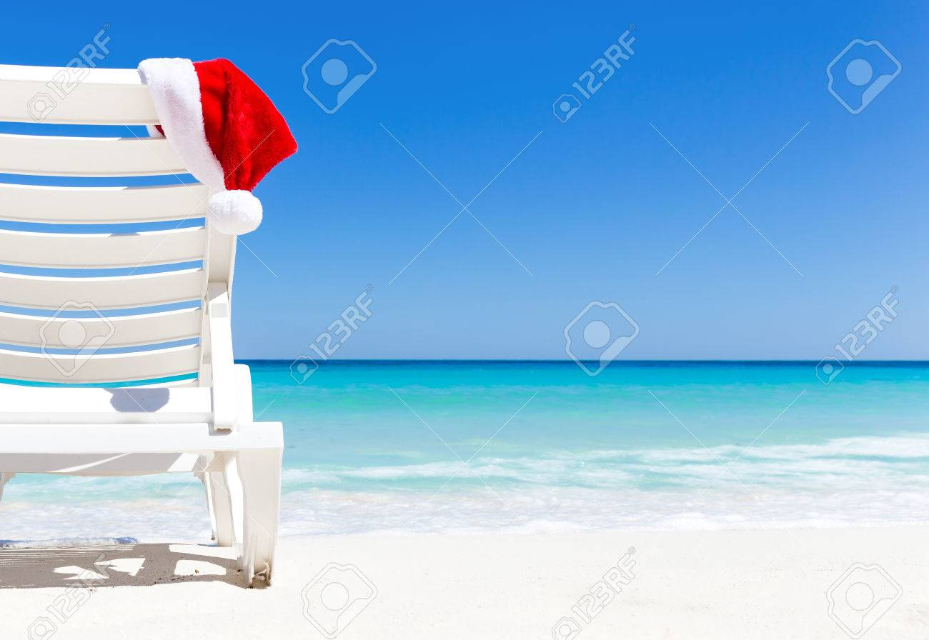 Santa Claus Hat on sunbed near  tropical calm beach with turquoise caribbean sea water and white sand. Christmas vacation concept Stock Photo - 50273820
