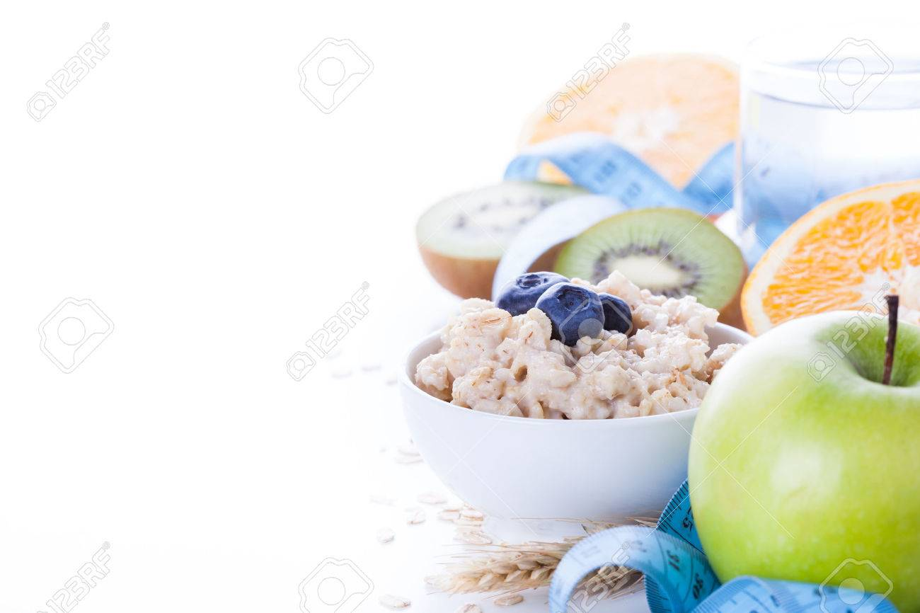 Morning healthy nutrition, diet frame with oatmeal porridge, fruits, mineral water and measuring tape. Perfect breakfast before workout Stock Photo - 50273908