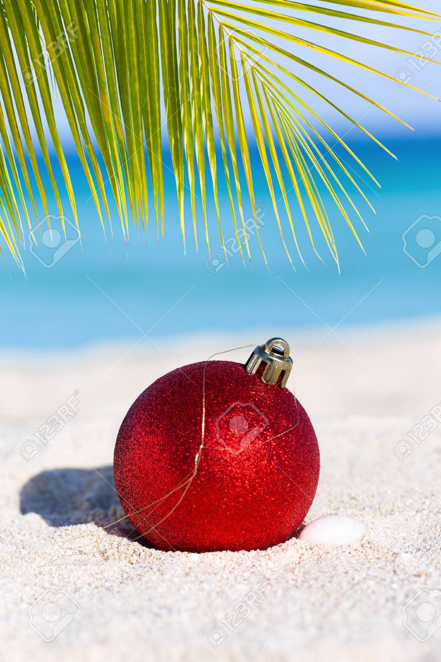 Tropical Christmas.Red Fir Tree Decoration Ball On Sandy Beach Tropical Christmas