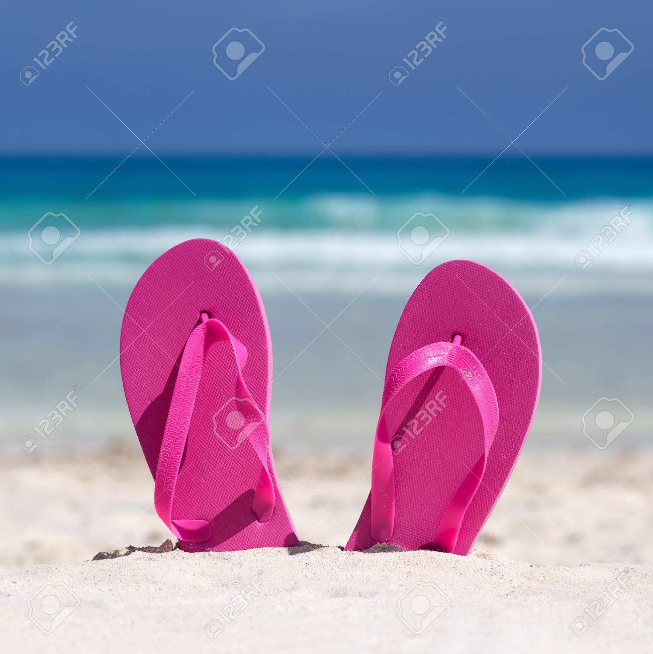 adea342350a4 Pink Flip Flops On White Sandy Beach Near Sea Waves