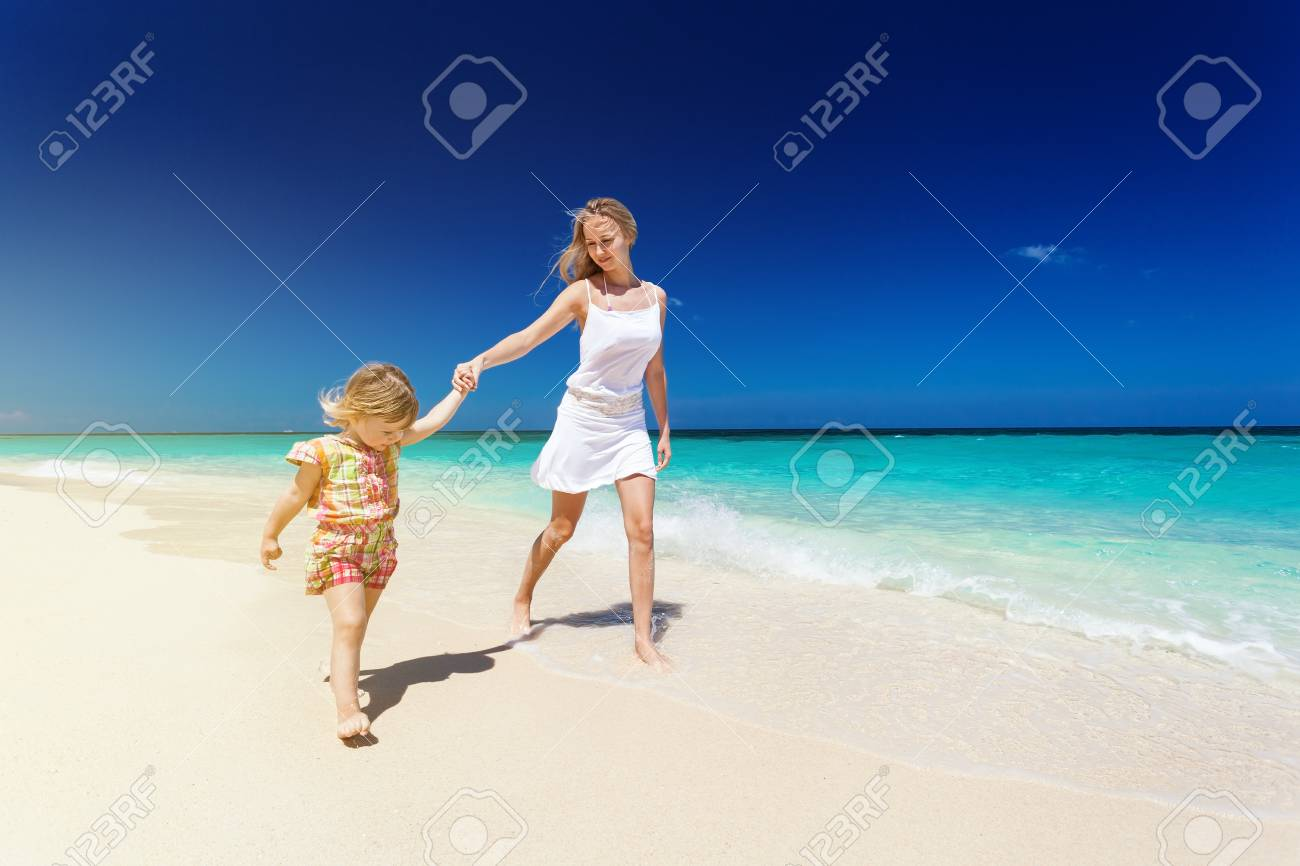 02ca628bb92e7 Mother and daughter having fun on white sandy beach, enjoying tropical  nature and summer vacation