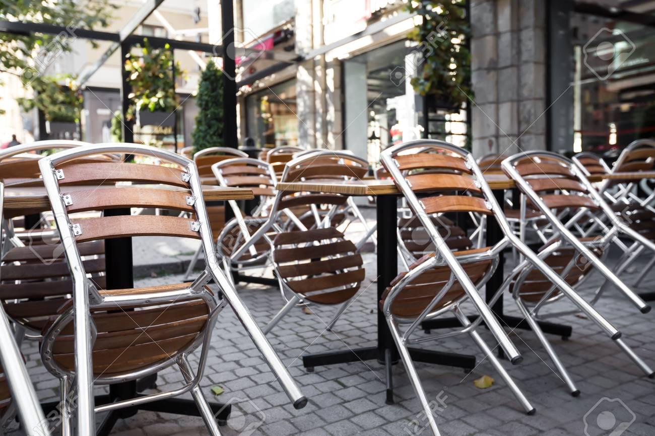 Caffè all\'aperto chiuso con sedie rovesciate sui tavoli, Nessuno