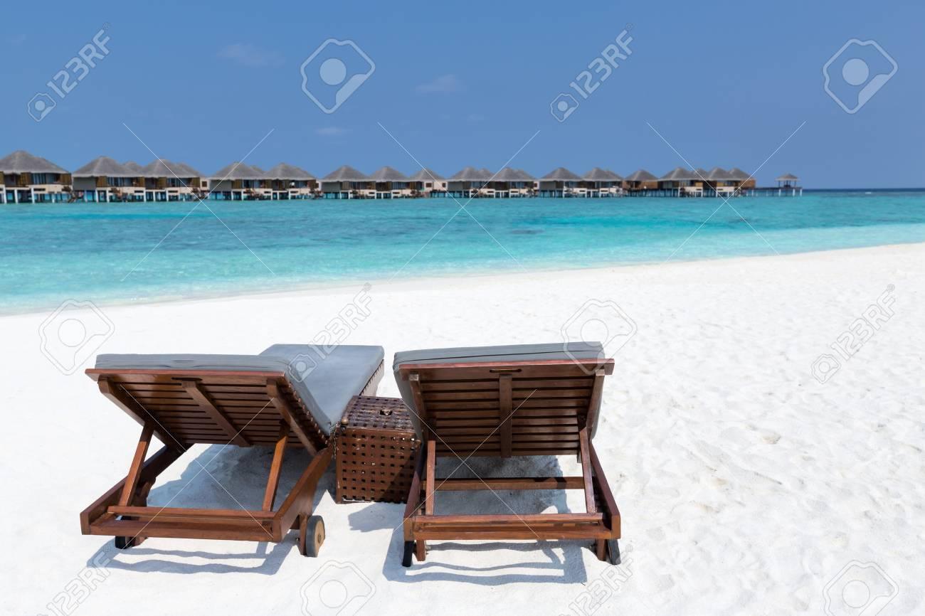 Lettini in legno sulla spiaggia incontaminata delle Maldive. Svuoti le  chaise longue sulla località di soggiorno tropicale con la vista sul mare e  le ...