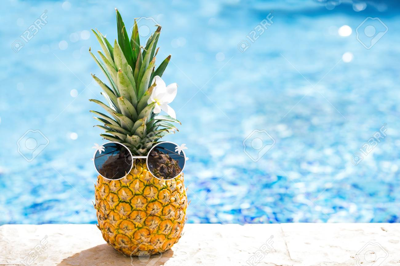 Funny happy pineapple in sunglasses on swimming pool background at tropical sunny day. Creative food and travel concept card with hipster ananas in glasses - 121767190