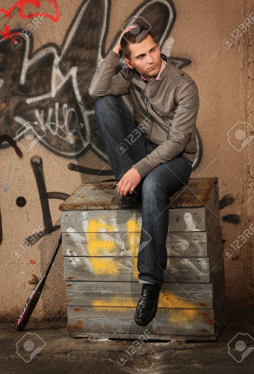 young guy sitting on the sand box ner painted wall Stock Photo - 8804211