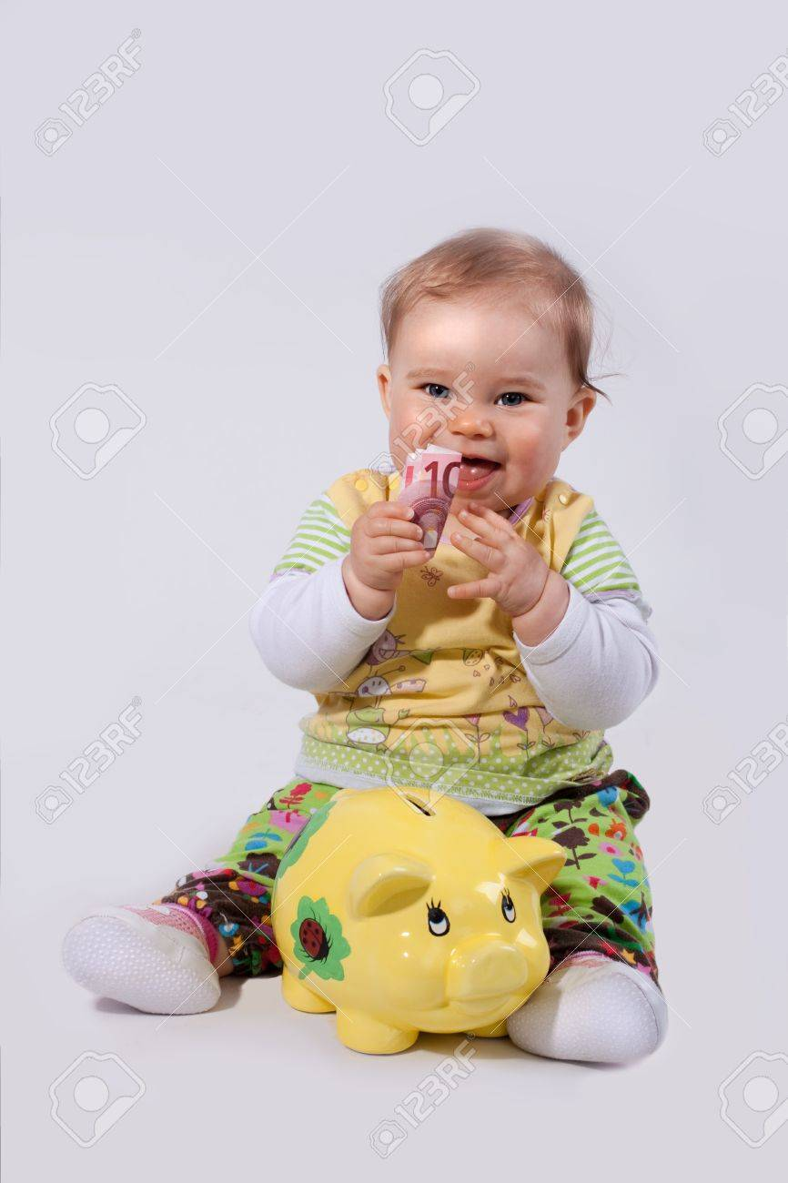 female baby smiles adorable with bank note in her hands - 13612394