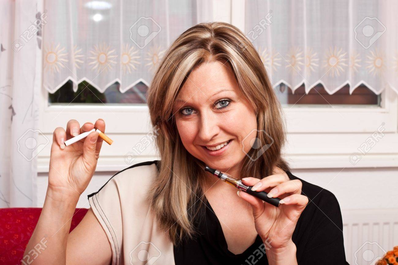 Blonde pretty woman chooses an electronic cigarette and destroys the normal Stock Photo - 14527949
