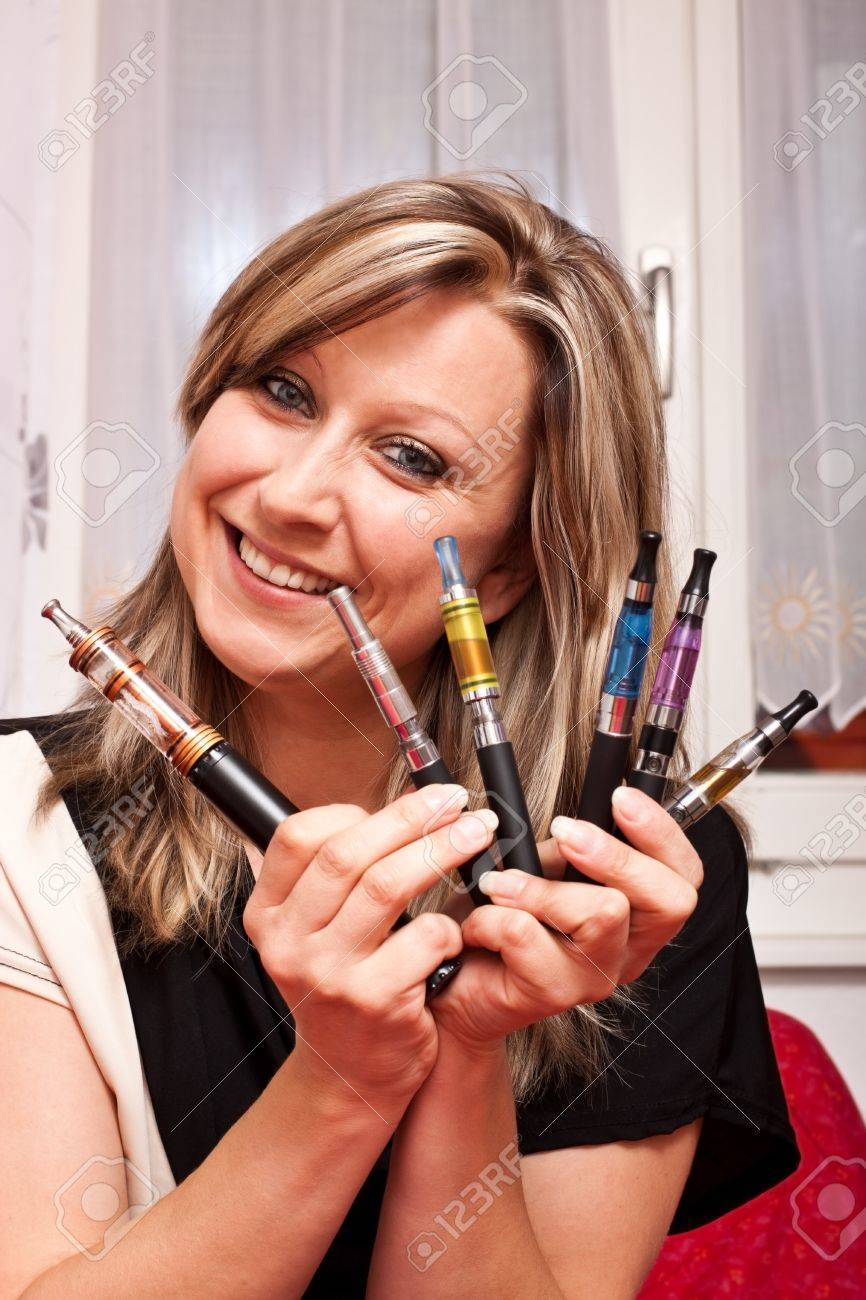 Young pretty woman shows multiple e-cigarettes and smiles Stock Photo - 14528023