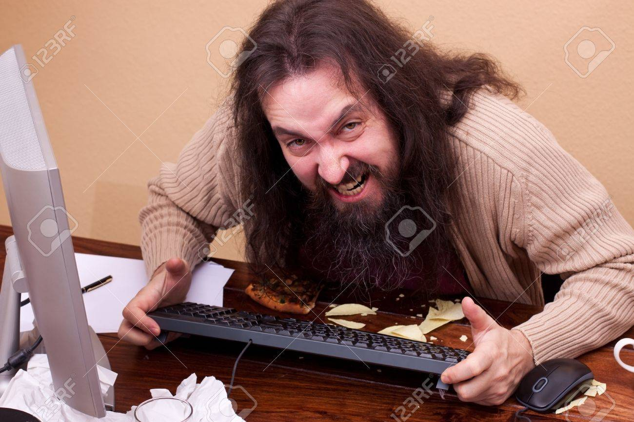 long haired angry nerd at a desk looking at viewer Stock Photo - 17643148