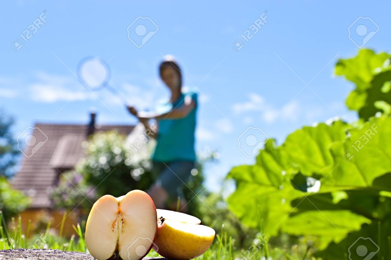 Young pretty woman with apple plays badminton Stock Photo - 20222868