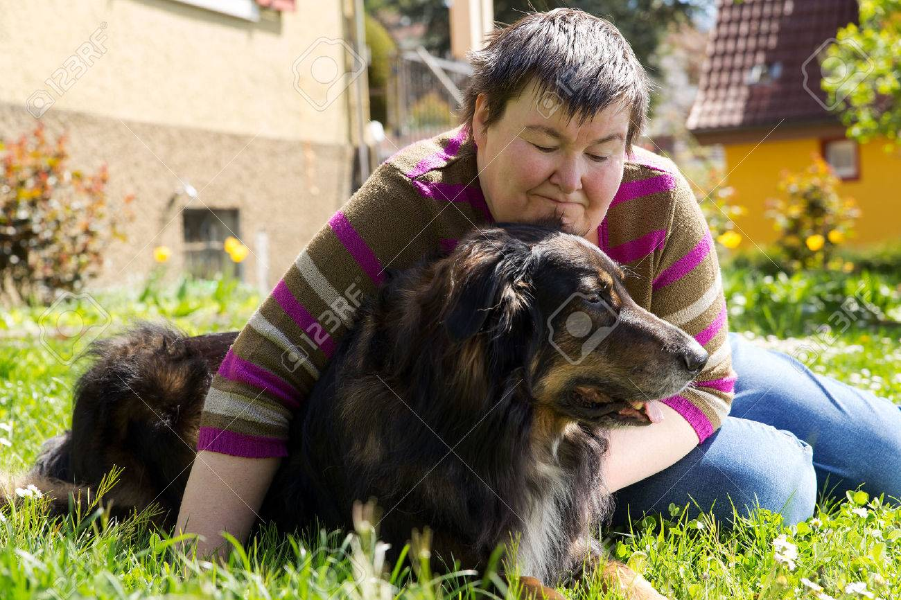 mentally disabled woman is lieing with dog on a lawn Stock Photo - 27664169