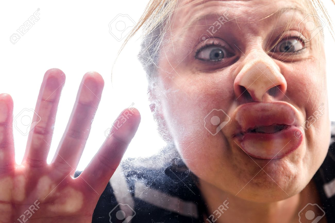 woman with fish mouth at the window makes a funny grimace - 54306363