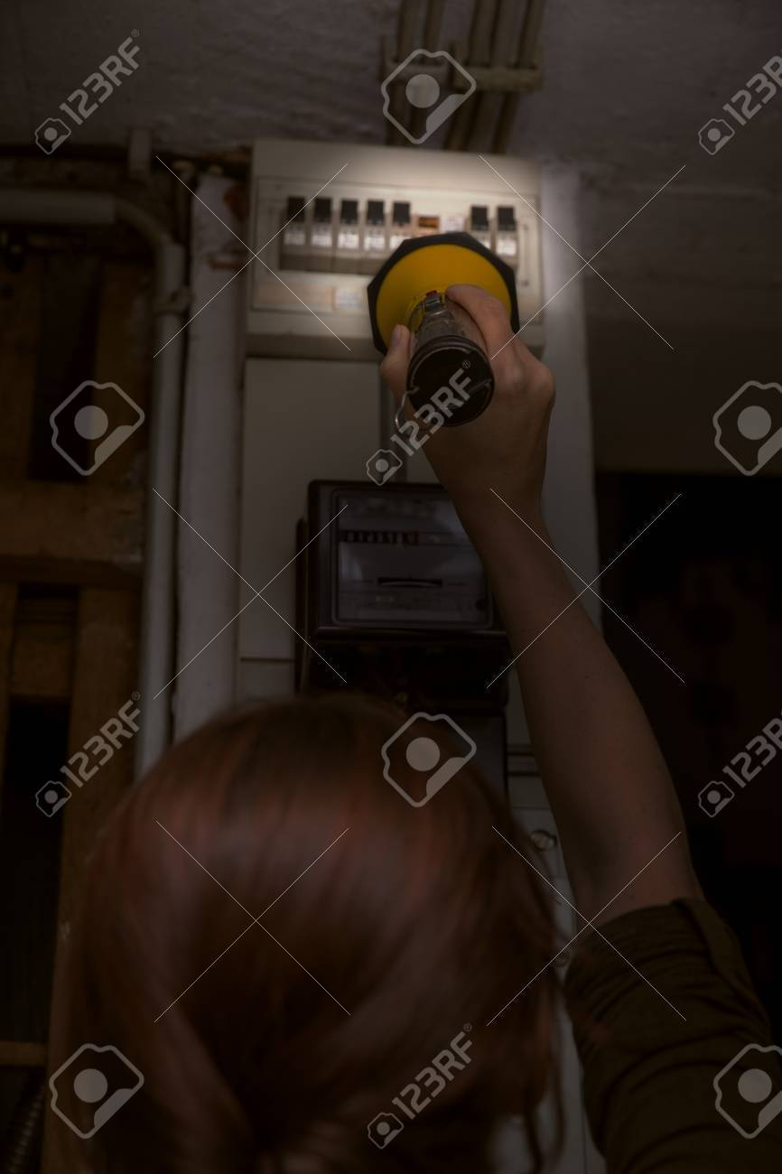... electricity cut, woman with flashlight checking the Blown Fuse in Breaker  Box blackout