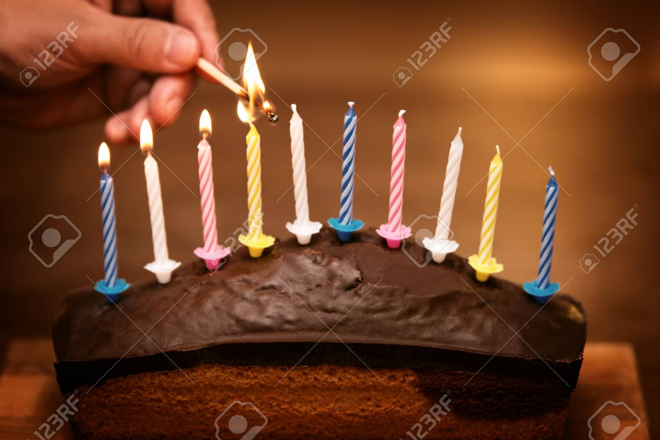 Man Lights Colorful Candles On A Birthday Marble Cake Stock Photo