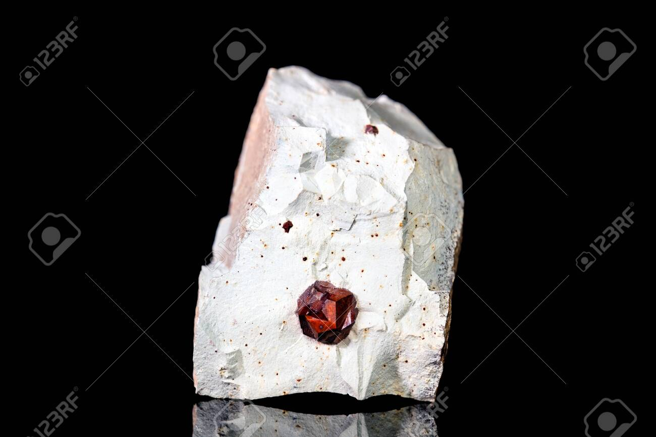 Raw garnet mineral stone on mother rock in front of black background, mineralogy and esotericism - 128004949