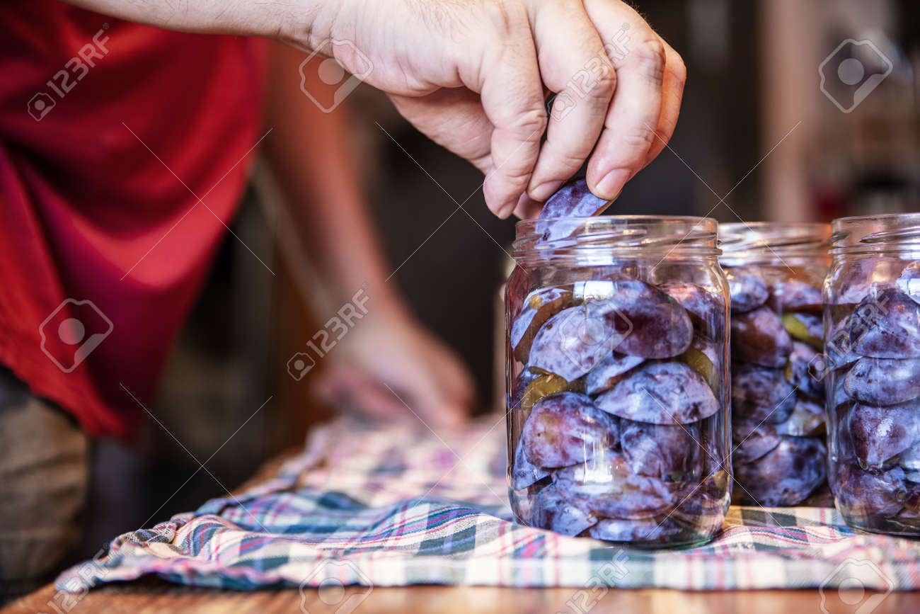 a man is filling glasses with plums, preparing for preserving the fruits, concept self supporter or gardening - 168974718