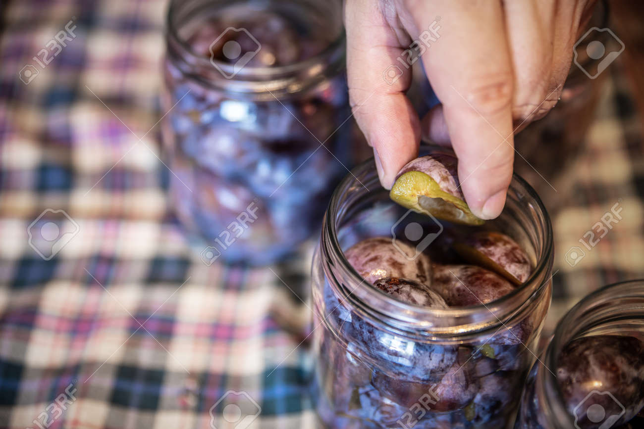 a man is filling glasses with plums, preparing for preserving the fruits, concept self supporter or gardening - 168974756