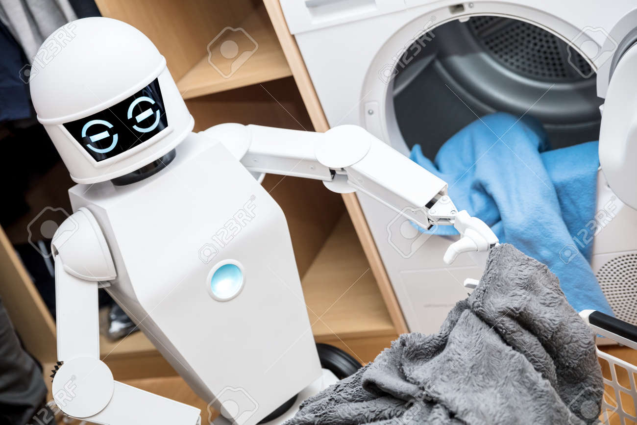 ambient assisted living robot or cyborg is working in the household. robot is putting some clothes in the dryer - 168974770
