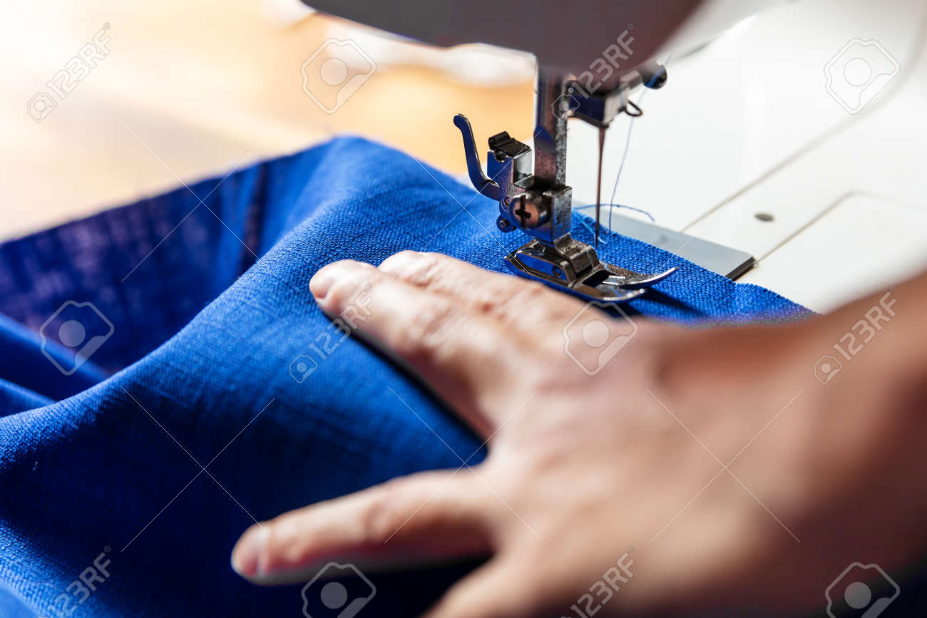 hand of a woman is working with blue linen on a sewing machine - 170381919