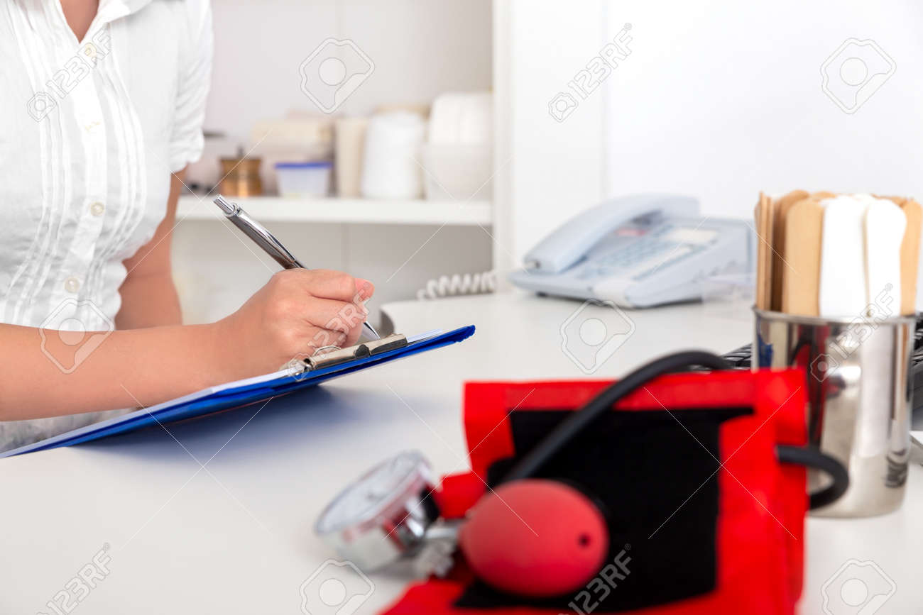 female doctor, nurse or secretary is doing some paperwork in the medical office - 170382649