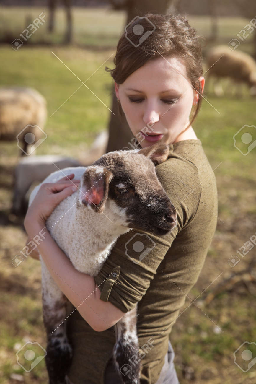 young woman holding a cute lamb, concept affectionate breeding and care - 170382680