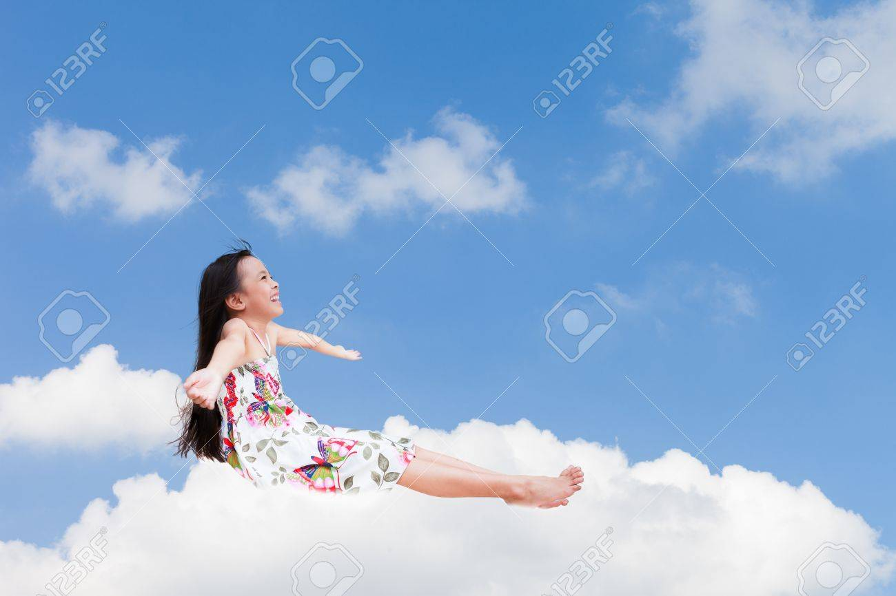 Smiling little girl sitting on the cloud over sky Stock Photo - 13544077