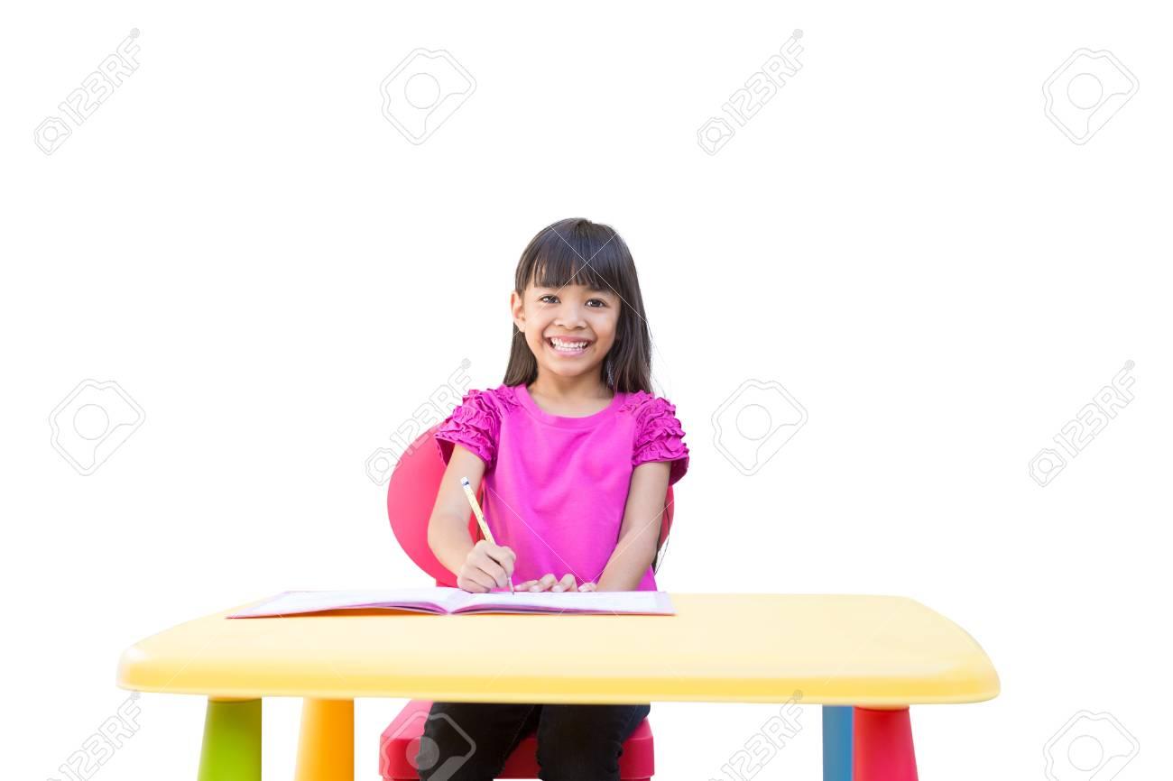 Souriant petite fille écrit sur le bureau isolé sur blanc banque