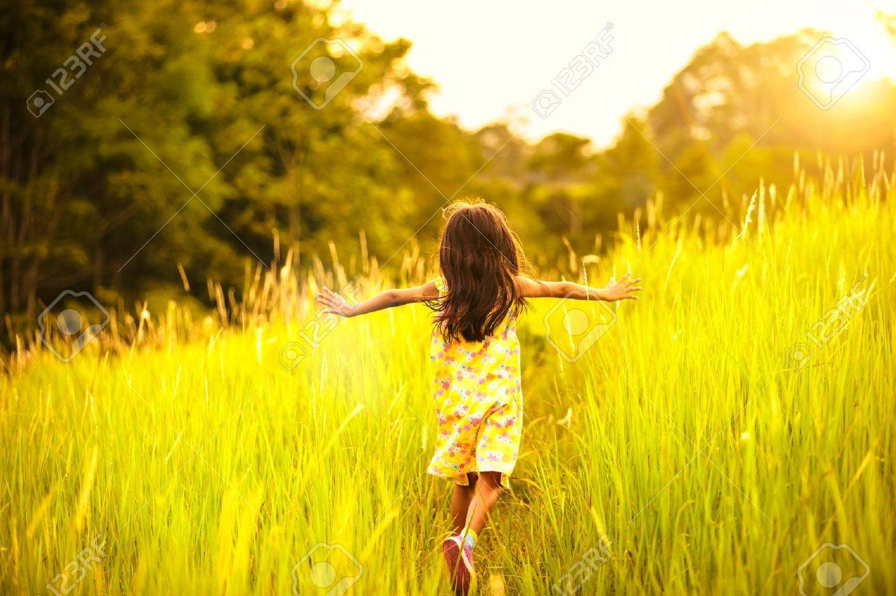 Little girl running on meadow with sunset Stock Photo - 20680108