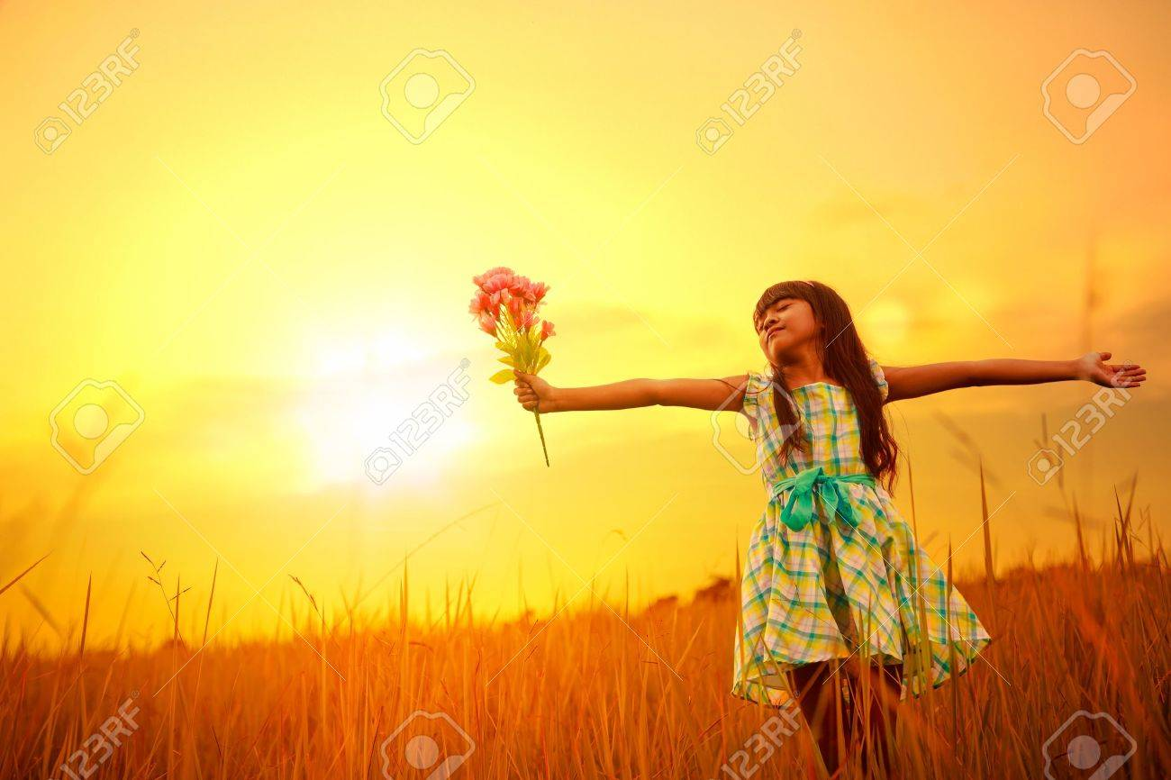 Little asian girl standing on countryside meadow and raised hands with sunset Stock Photo - 21198983