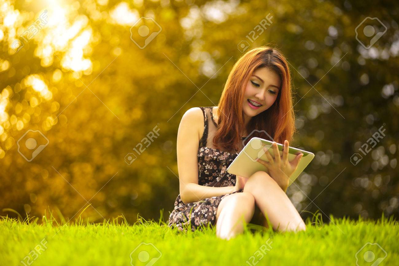 Asian woman using digital tablet in park, Outdoor Portrait Stock Photo - 22418839