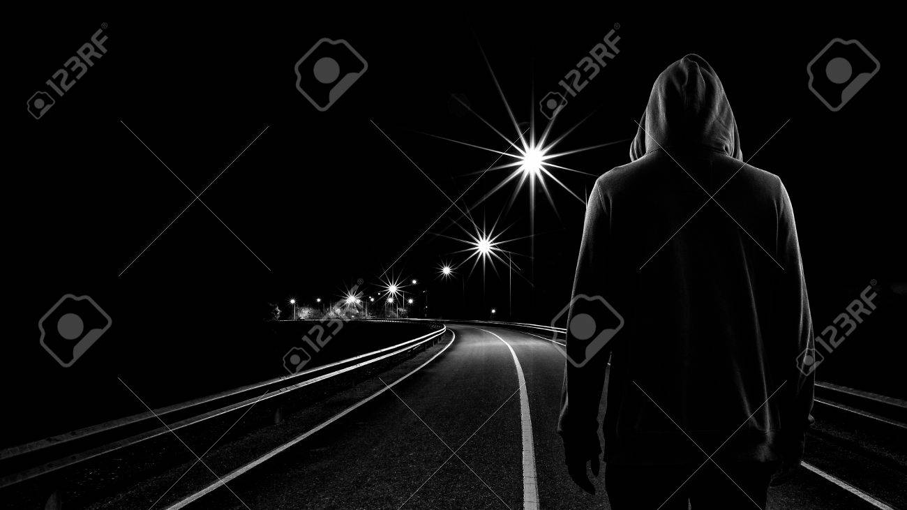 Stock photo teenager boy standing alone in the street at night black white tone