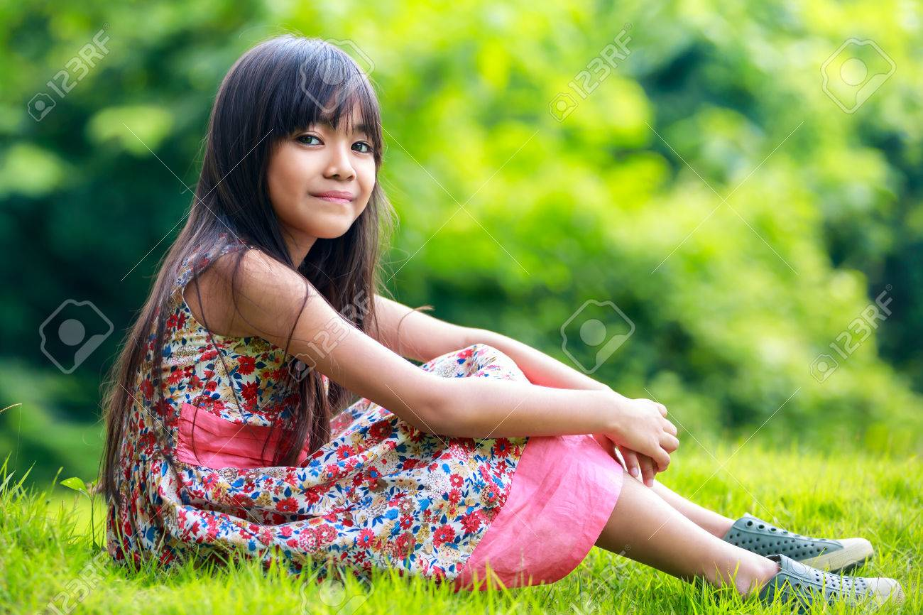 young asian girl sitting on the green grass in park stock photo
