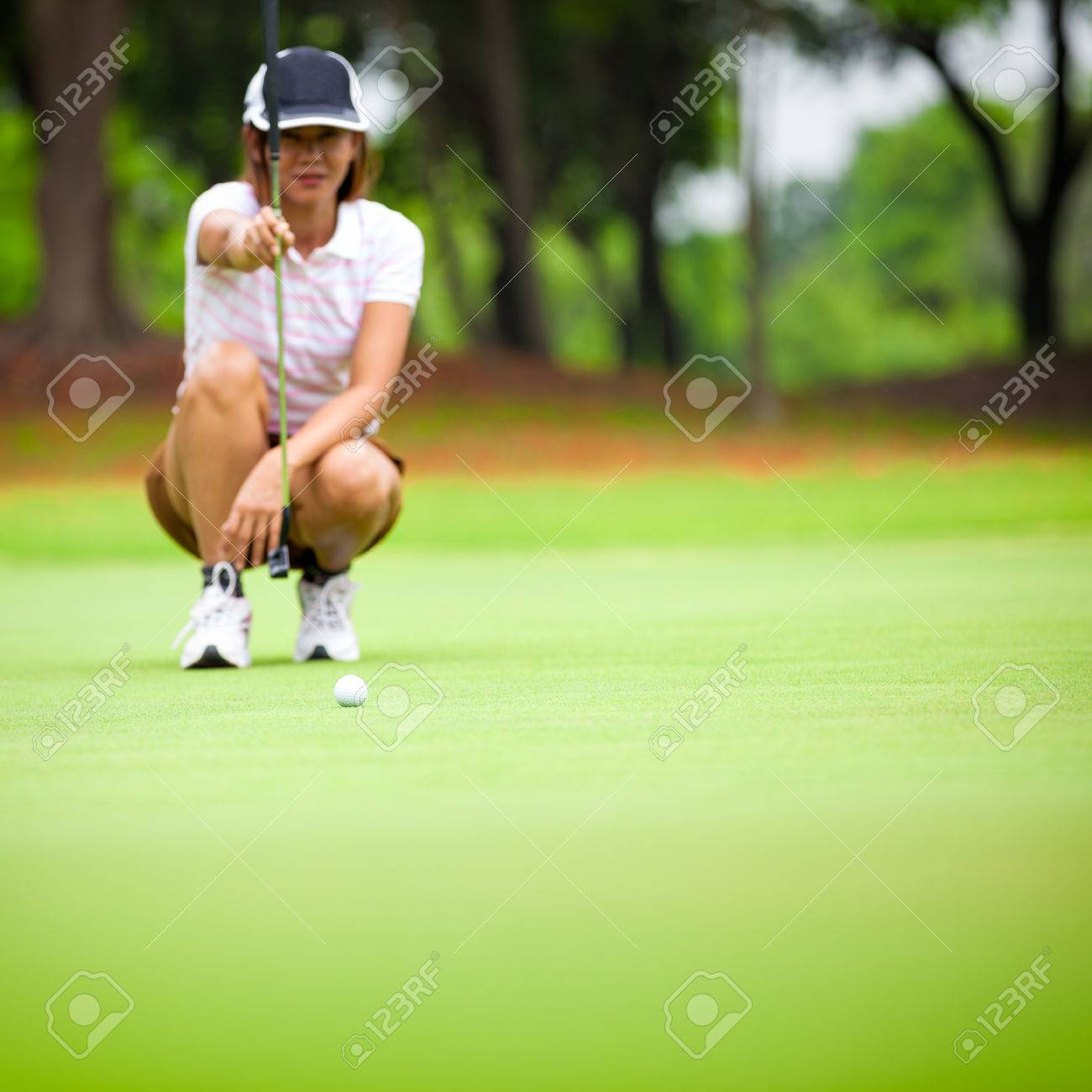 Female golf player with putter squatting to analyze the green at golf course, Select focus at golf ball Stock Photo - 26584394