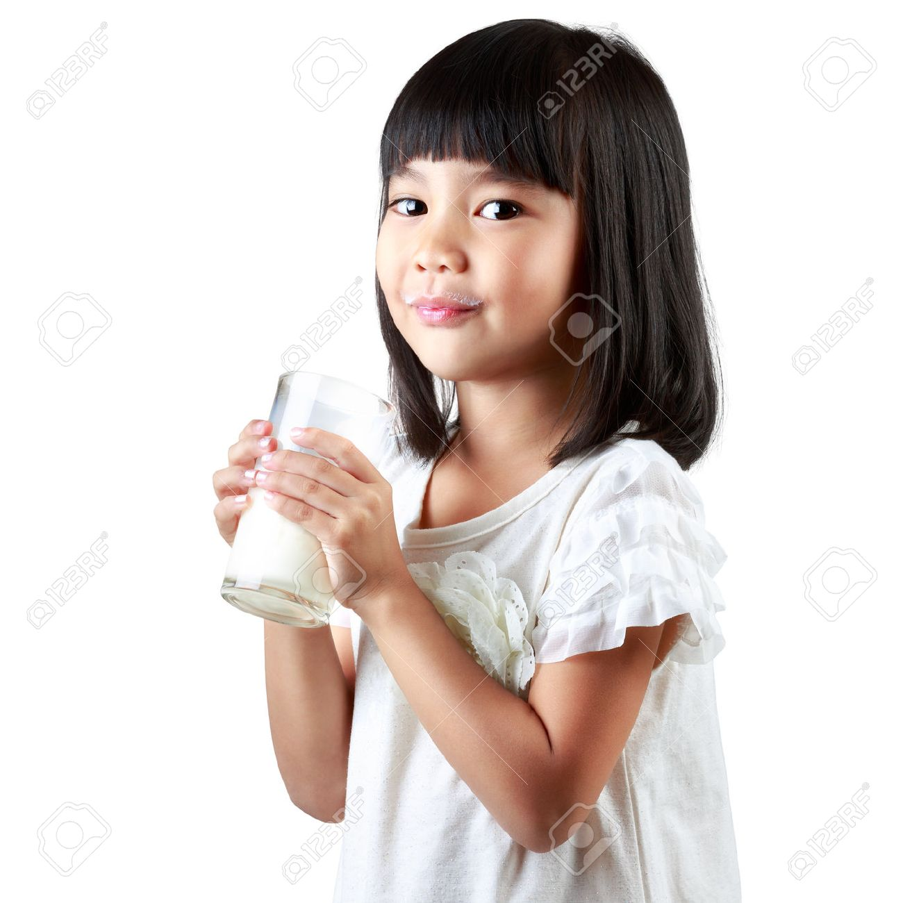 Happy Little Asian Girl Holding A Cup Of Milk Isolated Over White Stock Photo
