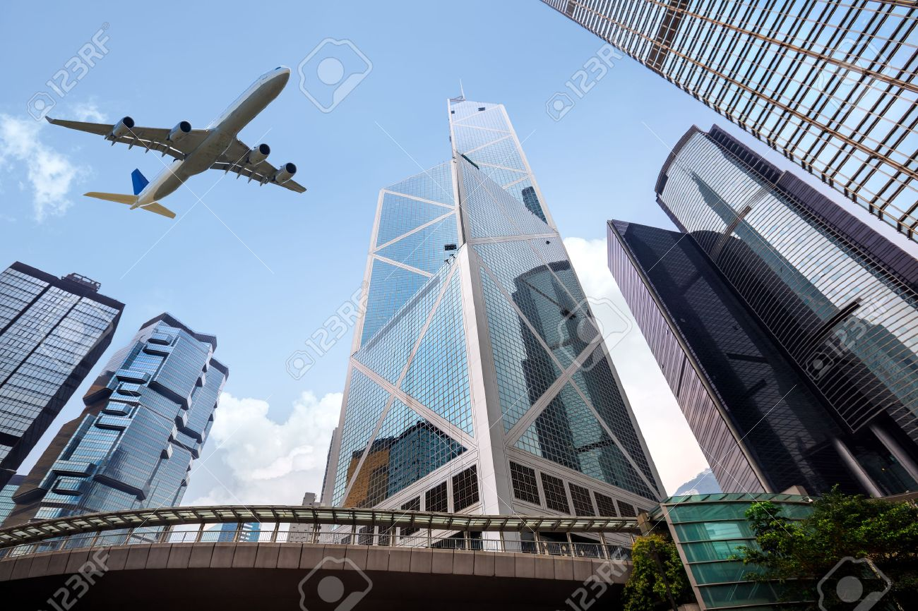 Tall City Buildings And A Plane Flying Overhead Hong Kong Stock
