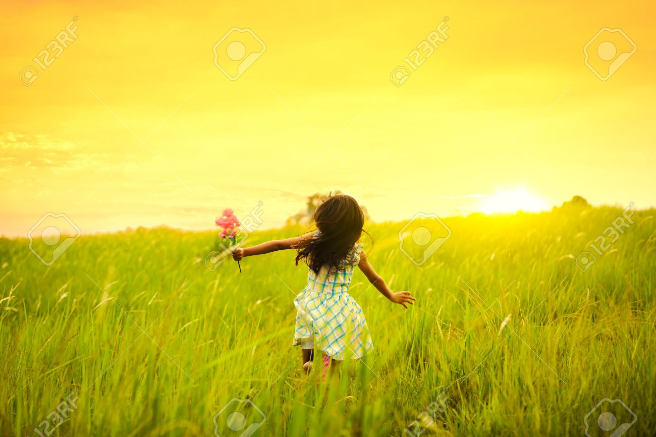 Little girl running on meadow with sunset Stock Photo - 40231888