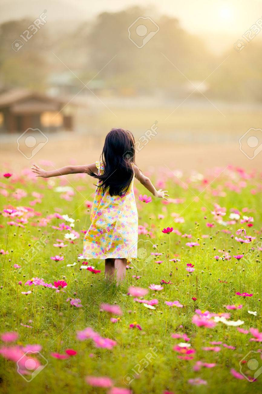 little girl running in the garden flowers on a clear day stock photo