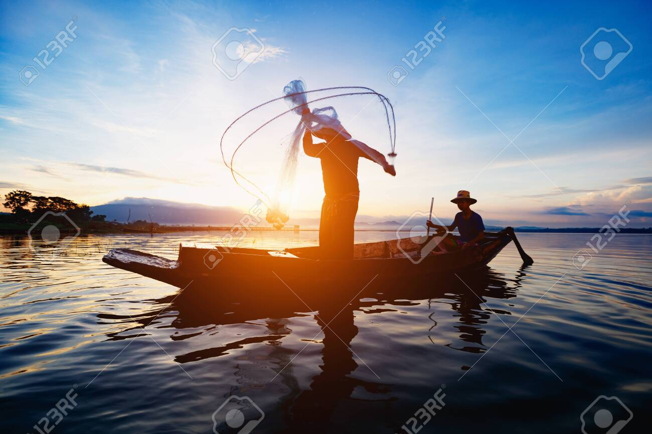 Silhouette of fishermen using nets to catch fish at the lake in the morning - 121622995